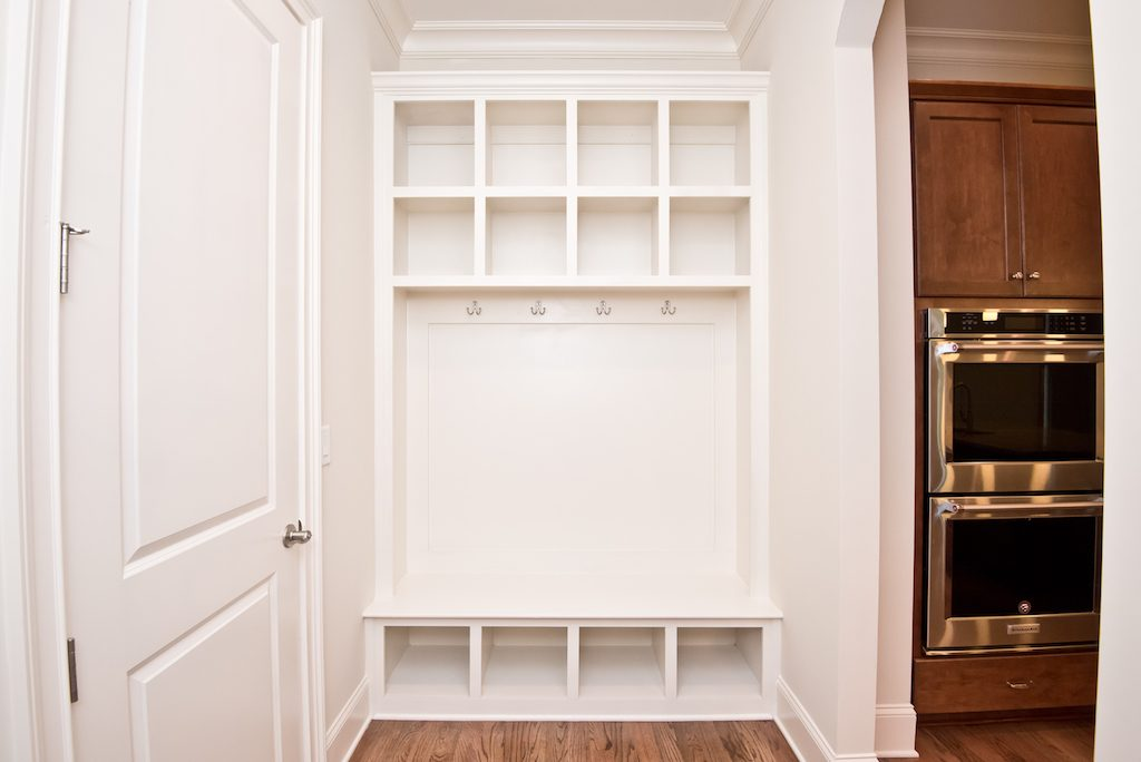 A built-in hall tree by the door to your garage gives you the perfect spot for storing coats, shoes, backpacks, and more.