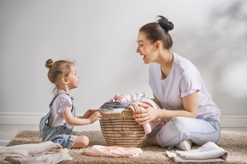 Mother and Daughter laughing and folding laundry