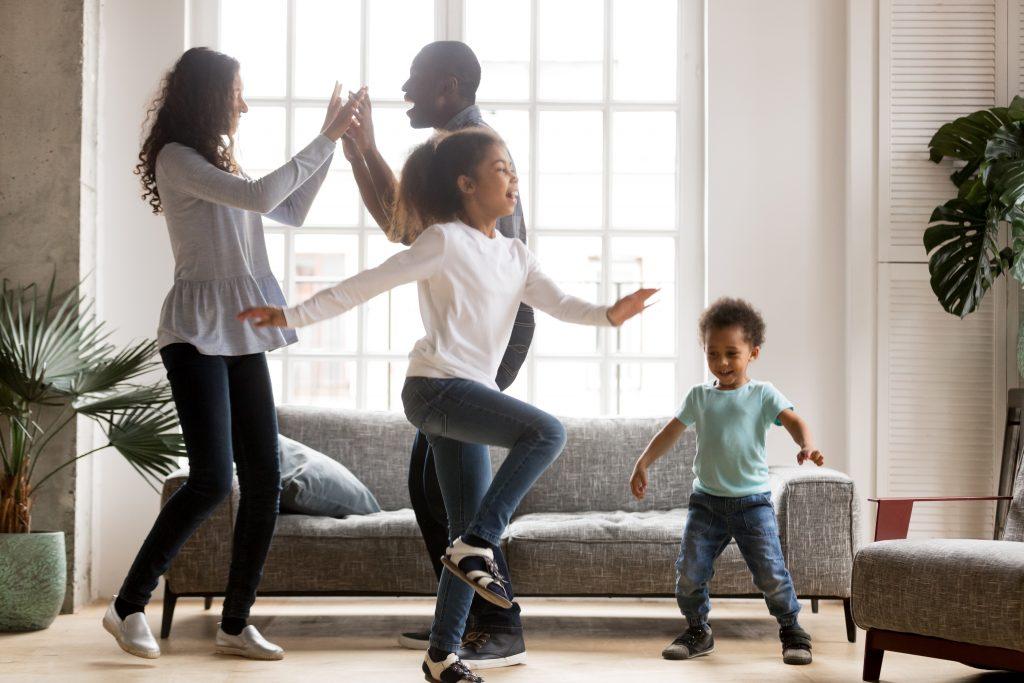 Happy family dancing in living room